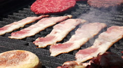 Coking meat on the grill: hamburger, bacon, bread, street food  Stock Footage