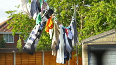 Clothes drying in the wind on a clothesline outside in the sun - stock footage