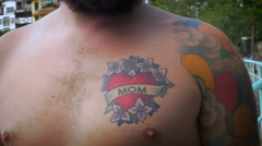 Portrait of a bearded man with a bare chest and a mom tattoo - RELEASED Stock Footage