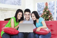 Group of friends using laptop on the sofa - stock photo