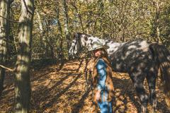Pretty girl standing by her grey horse Stock Photos