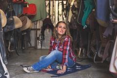 Pretty girl posing in equestrian context - stock photo