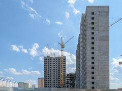 Tower crane on the construction of a new multi-storey house. Side view - stock photo