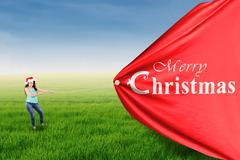 Indian woman pull a christmas banner - stock photo