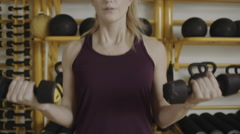 Young woman lifting weights in gym Stock Footage