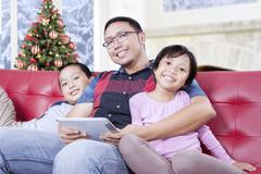Two kids and dad with tablet smiling at camera - stock photo