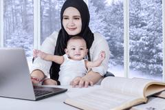 Young mother working with her baby - stock photo