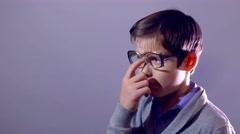 Boy teenager nerd portrait schoolboy tired rubs his forehead perspiring glasses Stock Footage