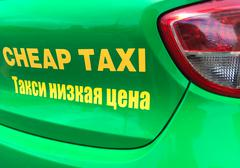 cheap taxi sign in English and Russian - stock photo