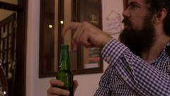 A bearded man orders a beer and is impatiently asking to have it opened Stock Footage