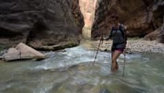 Woman Hiking in Water through the Zion Narrows Stock Footage