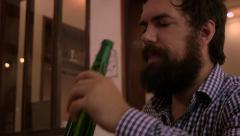 Hipster with a full beard orders a beer and takes a drink Stock Footage