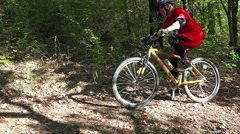 Mountain Bike traveling fast along autumn leaves forest track, crane shot Stock Footage