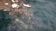 Flotsam and jetsam floating in slick polluted water Stock Footage