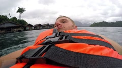 Young Man in Life Jacket Swimming in Lake Water Stock Footage