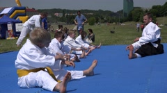 Stock Video Footage of aikido trainer make stretching exercises with children outdoor . 4K