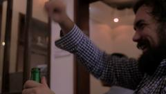 Bearded man drinking a beer and laughing out loud at a joke Stock Footage