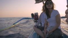 Stock Video Footage of Hand held 4k footage of three tourists on a small motor boat during sunrise