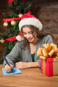 Beautiful girl writing New Year and Christmas congratulation - stock photo