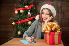Beautiful girl thinking about New Year and Christmas congratulation - stock photo