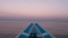 Peaceful footage of the bow of a boat on calm water during sunrise Stock Footage