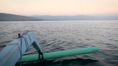 Boat skimming the surface of water with mountains in the background Stock Footage