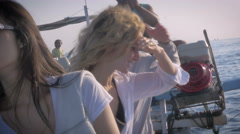 Beautiful Asian woman and other tourists looking around on a boat Stock Footage