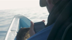 A man checks his phone while sitting at the front of a small boat Stock Footage