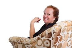 Smiling Senior Woman Sitting on Couch Stock Photos