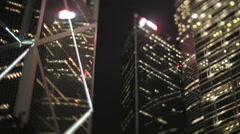 Tilt-shift shot looking up at brightly lit offices at night, Hong Kong - stock footage