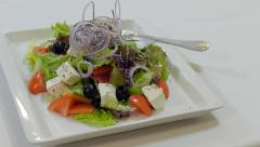 Waiter Puts A Plate With Greek Salad  On A Table Stock Footage