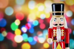 Soldier nutcracker statue standing in front of Christmas lights - stock photo