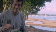 Attractive middle aged man and young woman drink coffee at cafe on the beach Stock Footage