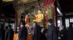 elderly female belivers chanting around a Buddha - stock footage