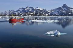 Red freighter cruising through Kong Oscars Havn Ammassalik Island Kalaallit - stock photo