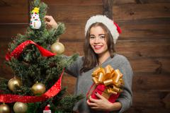 Stock Photo of Beautiful girl decorating New Year tree at home