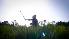 Silhouette of a young couple using a selfie stick in tall grass Stock Footage
