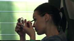 Stock Video Footage of Young woman applying crayon while sitting on a train, shot at 240fps HD