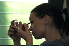 Stock Video Footage of Young woman applying crayon while sitting on a train, shot at 240fps NTSC