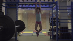 Young woman doing monkey bar exercises in fitness Centre Stock Footage