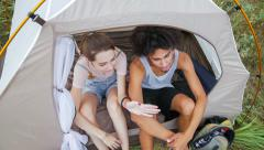 Young couple sitting their tent, huddled together, talks on various topics Stock Footage