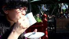 Woman drinking milk tea in the afternoon sunshine - stock footage