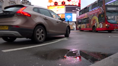 London motor traffic through picadilly circus with lights reflected in puddle Stock Footage