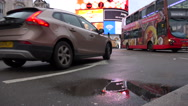 Stock Video Footage of London motor traffic through picadilly circus with lights reflected in puddle
