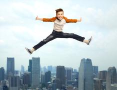 Stock Photo of happy smiling boy jumping in air
