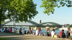 4K UHD Cologne Köln Rhine river promenade people sitting chatting relaxing Stock Footage
