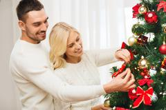 Stock Photo of happy couple decorating christmas tree at home