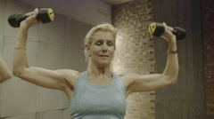 Mature Adult women exercising weights in gym - stock footage