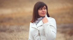 woman girl in autumn coat on nature of the wind is blowing brown background - stock footage