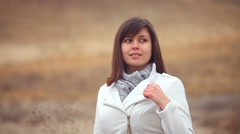 girl woman in autumn coat on nature of the wind is blowing brown background - stock footage